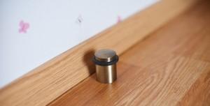 Напольный ограничитель двери с широким основанием крепится к стяжке а не ламинату