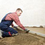 Мужчина выравнивает цемент